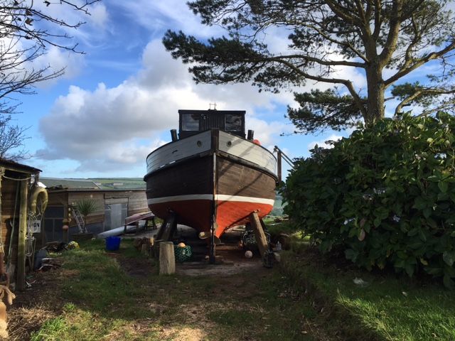 Fishing trawler on a farm waiting to be converted into a tiny home