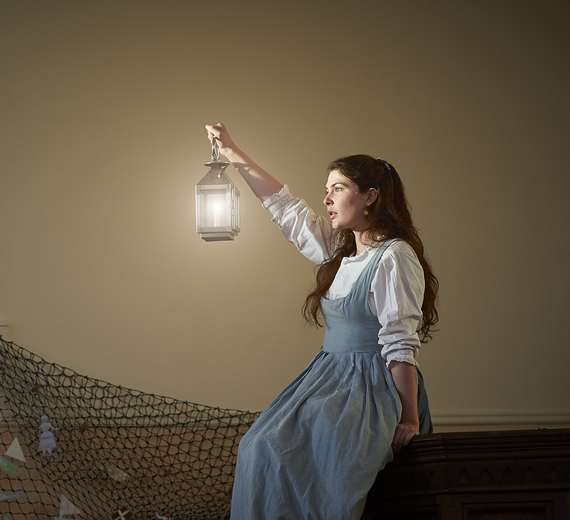 picture of the play the coastguards daughter, girl with a lantern wearing a blue dress and holding a lantern