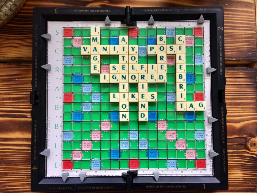 social media and words associated with social media spelled out with scrabble letters on a travel scrabble board on top of a wooden table